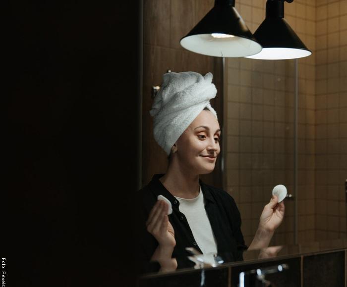 Foto de una mujer limpiando su cara frente a un espejo