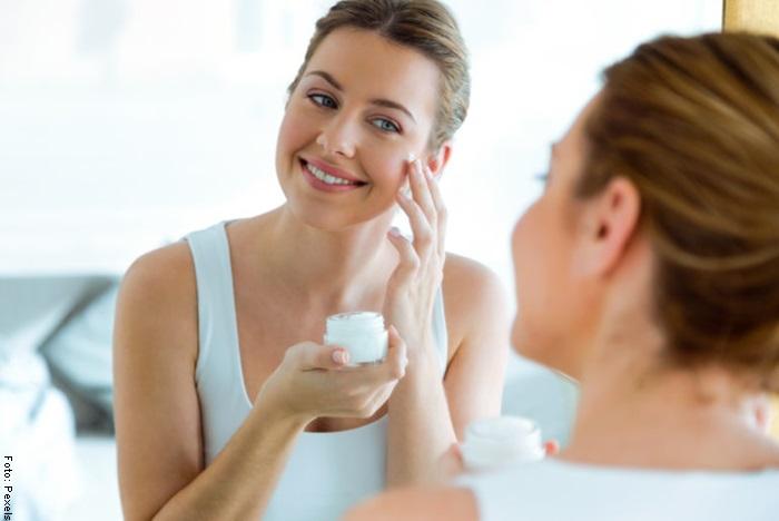 Foto de una mujer aplicándose crema hidratante