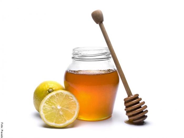 Foto de un frasco de miel con un limón cortado a la mitad