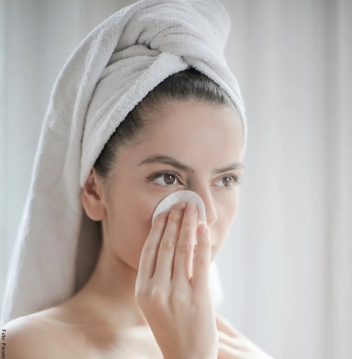 Foto de una mujer en el baño limpiando su rostro
