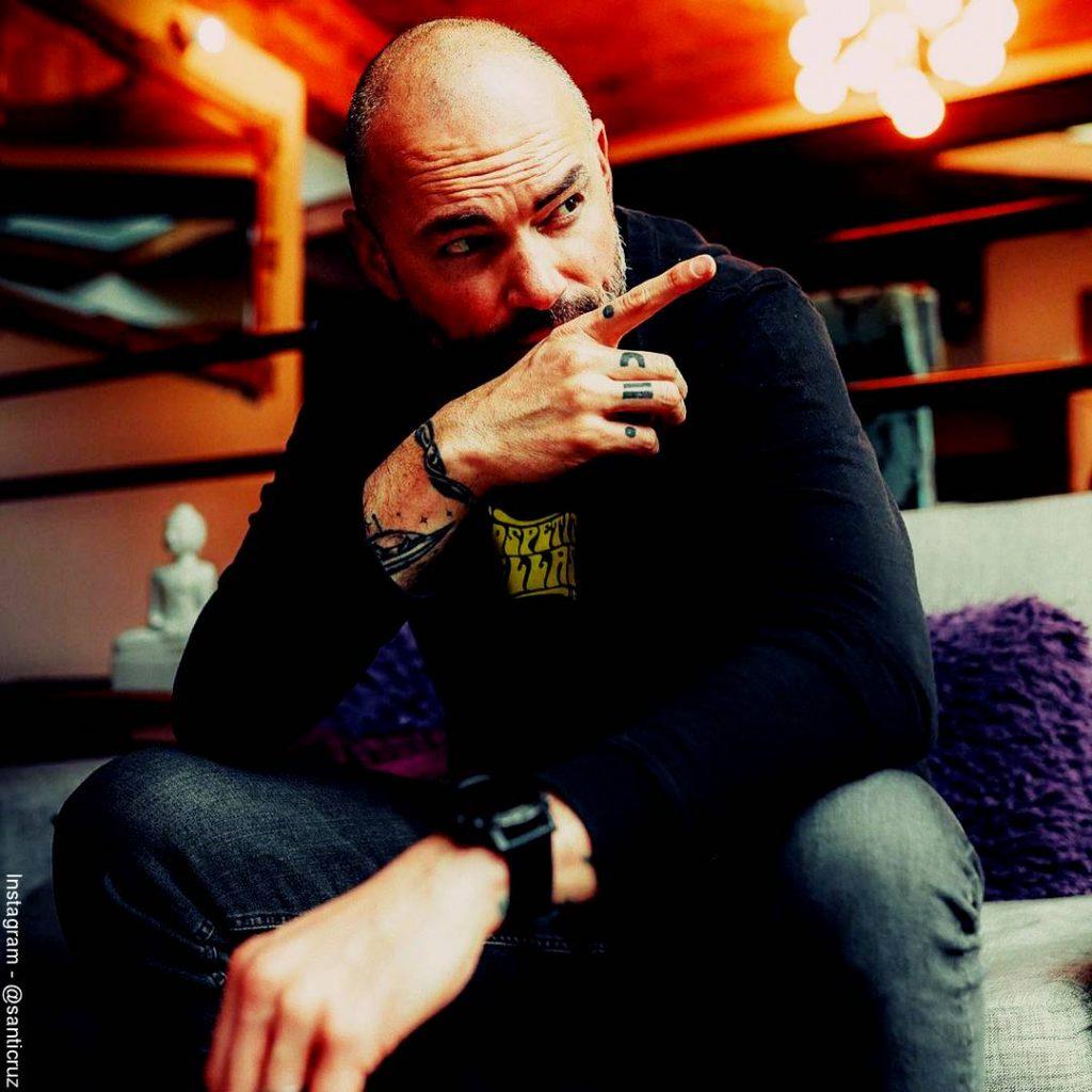 Foto de Santiago Cruz señalando con su dedo índice la pared