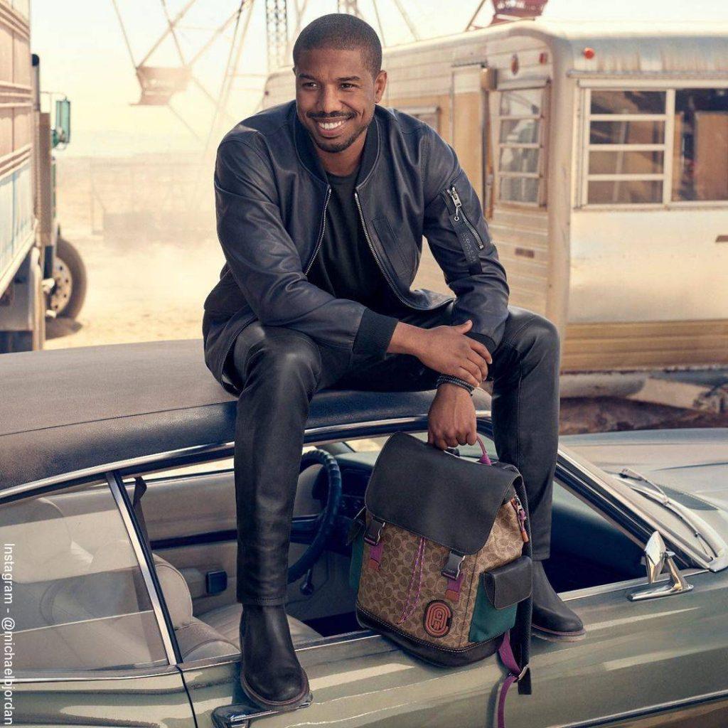 Foto de Michael B. Jordan sentado sobre un carro