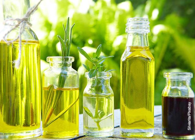 Foto de unos recipientes con aceite y plantas naturales