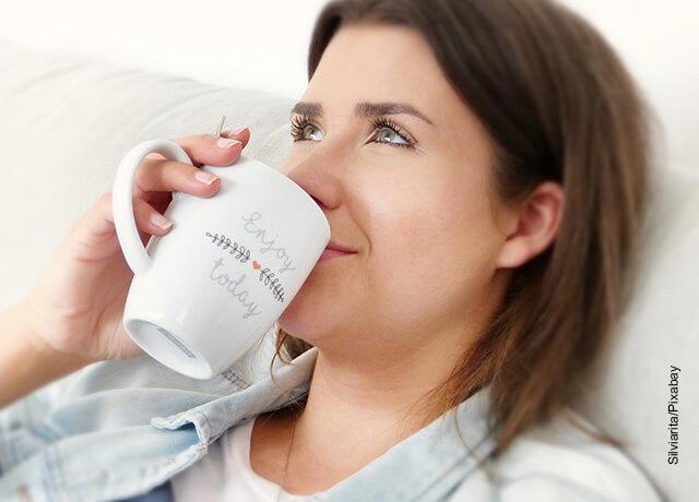 Foto de una mujer tomando una bebida en pocillo