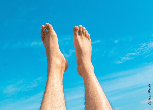 Foto de los pies de un hombre elevados al cielo