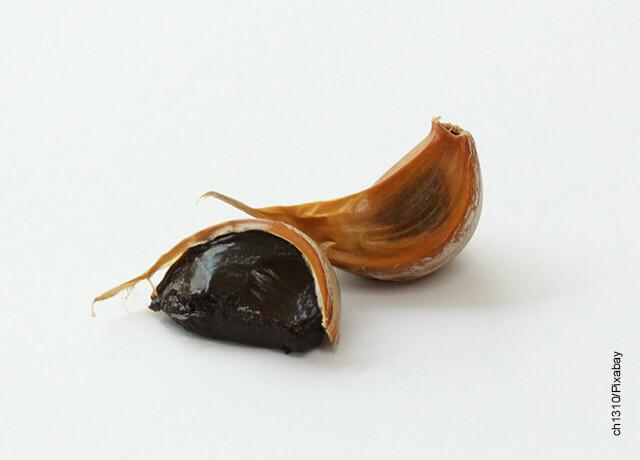 Foto de un diente de ajo negro sobre una mesa