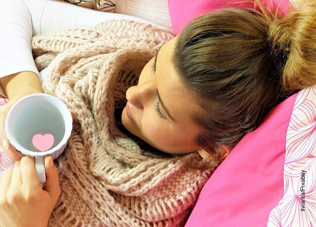 Foto de una mujer tomando una taza de agua caliente