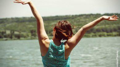 Foto de mujer de espaldas abriendo los brazos