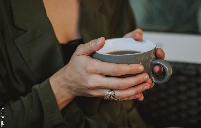 Foto de una mujer con una taza de té para ilustrar para qué sirve el orégano