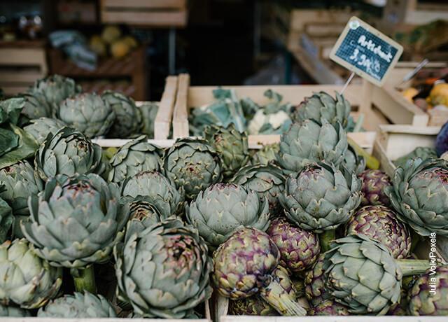 Foto de alcachofas en el mercado que muestran para qué sirve la alcachofa