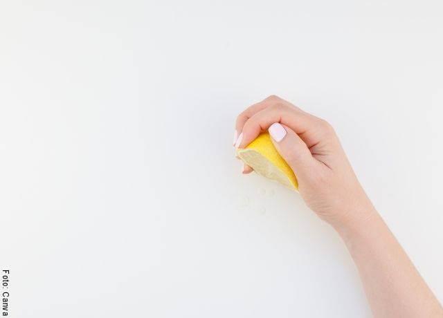 Foto de una mano exprimiendo un limón