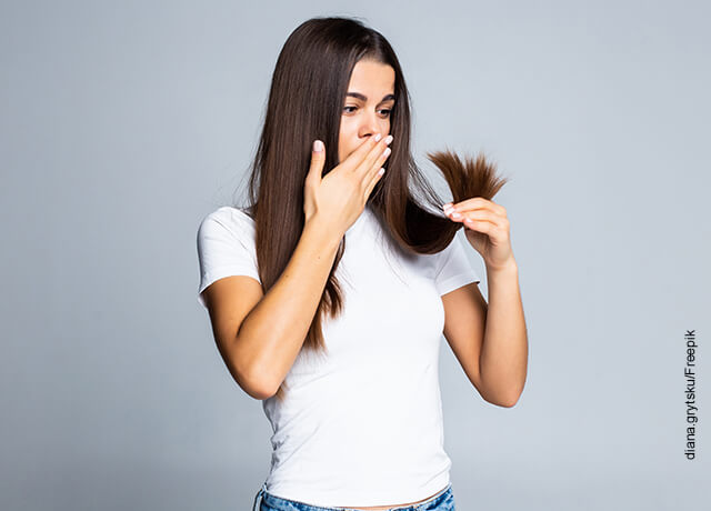 Foto de una mujer mirando asustada que muestra por qué se cae el cabello