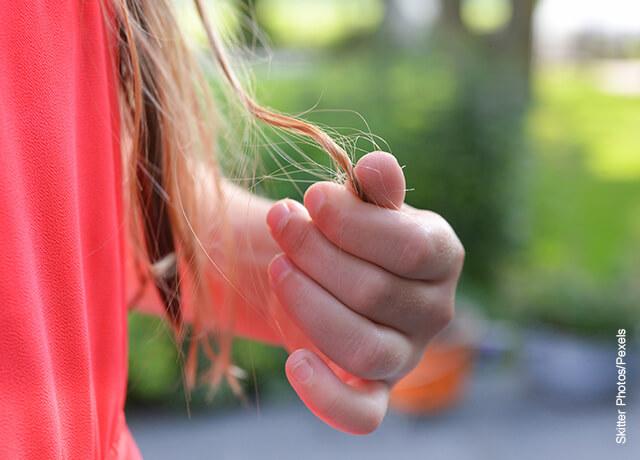 Foto de una chica tomándose las puntas del pelo