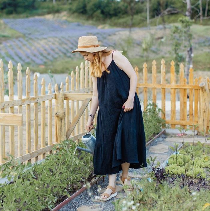 Foto de una mujer regando un jardín
