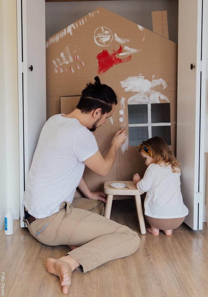 Foto de un hombre con una niña pintando un cartón