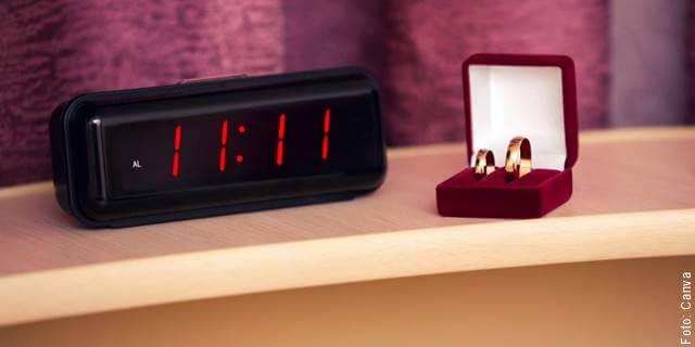 Foto de la hora 11:11 en un reloj digital junto a unas argollas de matrimonio