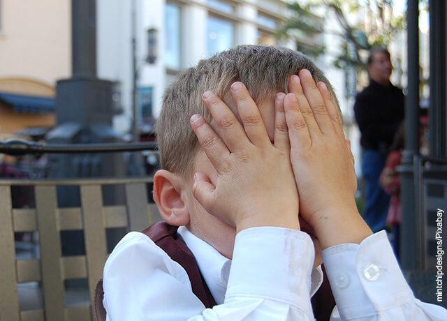 Foto de niño tapándose la cara de vergüenza