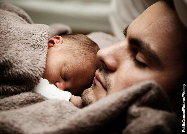 Foto de hombre durmiendo con un bebé