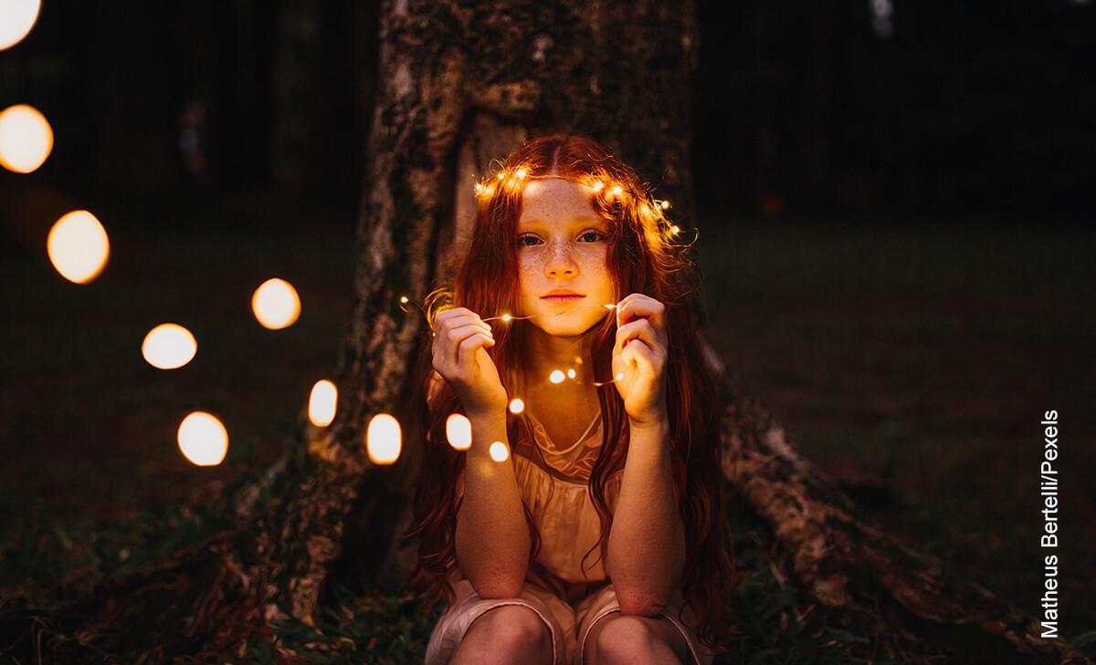 Foto de niña sentada en el bosque sosteniendo unos bombillos