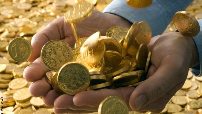 Foto de unas manos sosteniendo monedas de oro