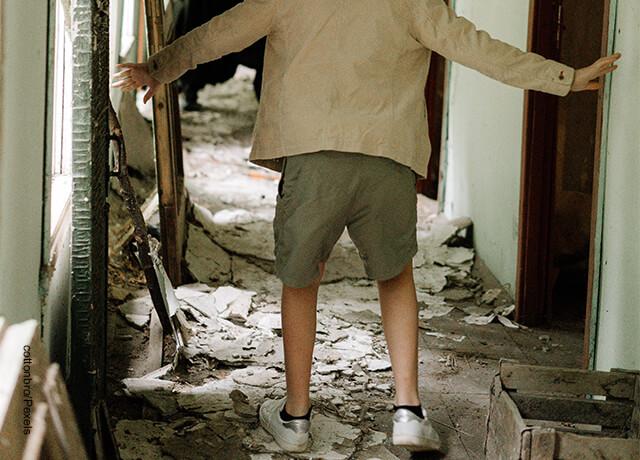 Foto de una persona en media de las ruinas de una casa