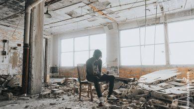 Foto de un hombre sentado entre ruinas de una casa
