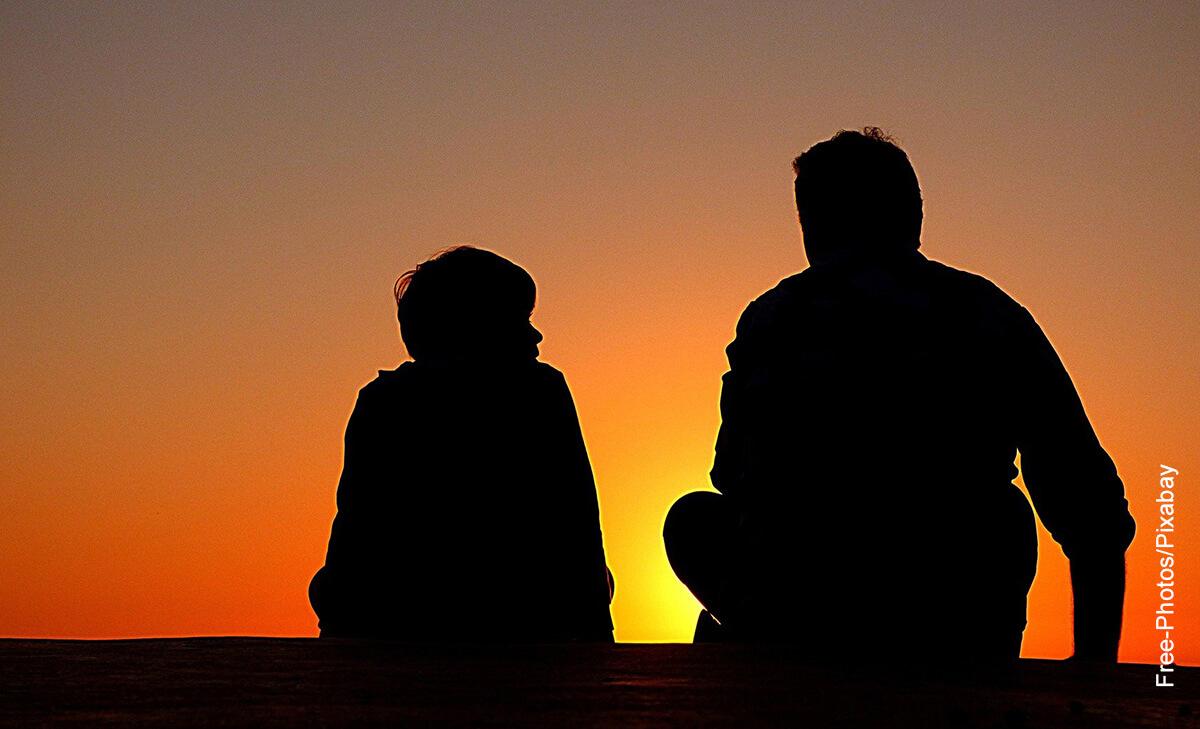 Foto de un hombre hablando con un niño al atardecer