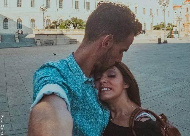 Foto de una pareja tomándose una selfie y él le está dando un beso en la frente a ella