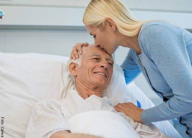 Foto de una señora visitando a un anciano en el hospital