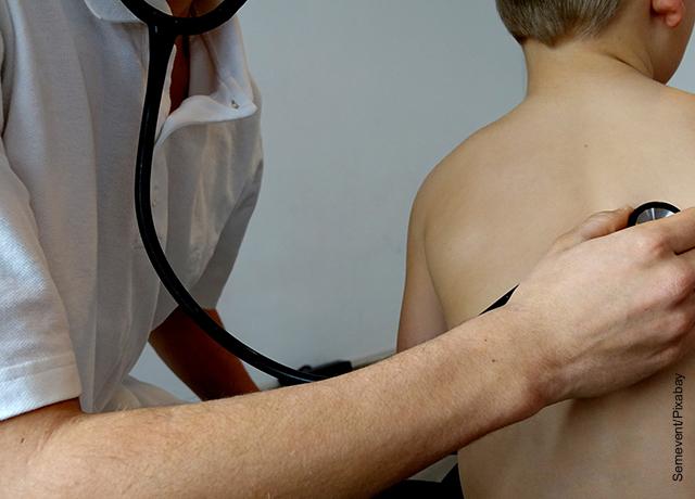 Foto de un niño siendo evaluado por un doctor