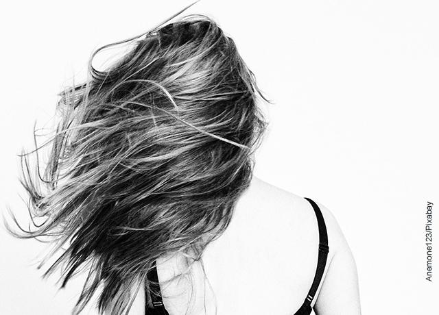 Foto de una mujer de espalda moviendo su cabeza que ilustras la sábila para el cabello