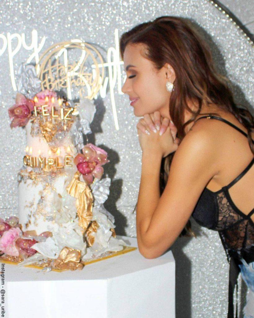 Foto de Sara Uribe con los ojos cerrados frente a su torta de cumpleaños.