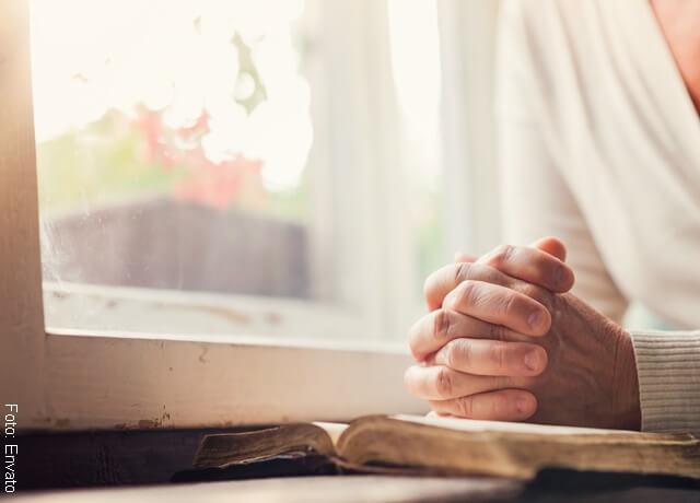 Foto de persona rezando con la biblia