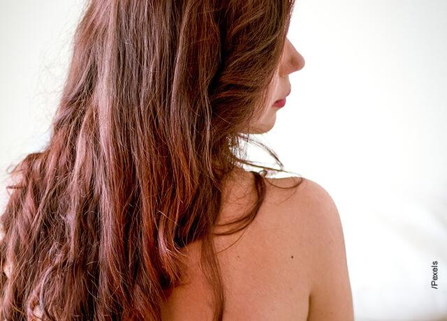 Foto de una mujer de espalda de cabello rojizo