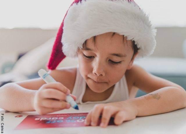 Foto de un niño escribiendo y con gorro navideño