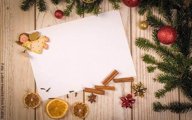 Foto de una hoja de papel rodeada de adornos navideños