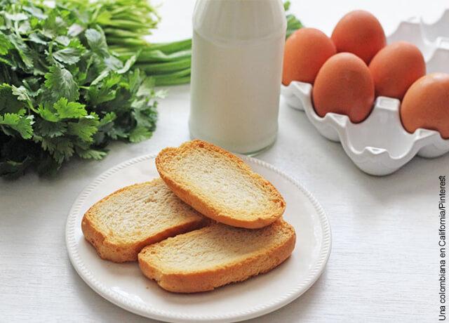 Foto de una botella de leche, huevos, tostadas y cilantro sobre una mesa