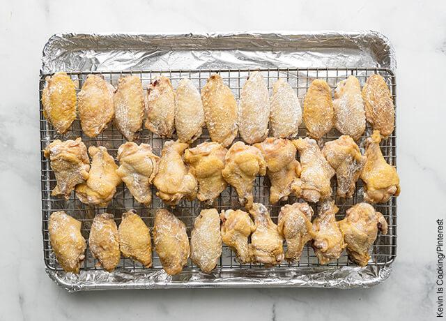 Foto de piezas de pollo sobre una rejilla de horno que ilustra cómo hacer alitas bbq