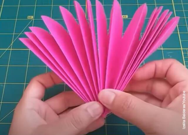 Foto de unas manos extendiendo un papel rosado que muestra cómo hacer flores en cartulina