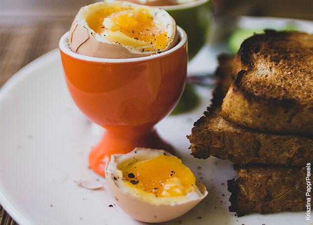Foto de un desayuno con huevo tibio y pan tostado
