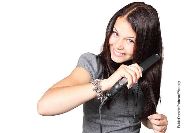 Foto de una mujer planchando su pelo que muestra cómo hacer ondas en el cabello