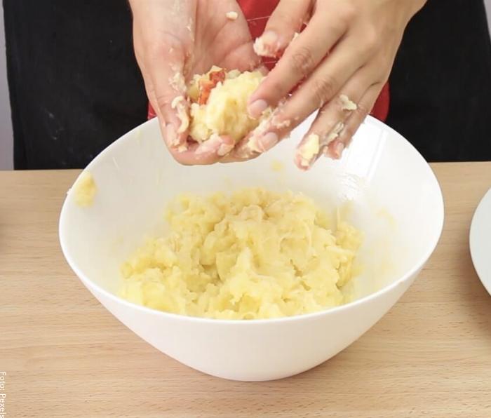 Foto de una mujer haciendo bolitas de papa para ilustrar cómo hacer papas rellenas