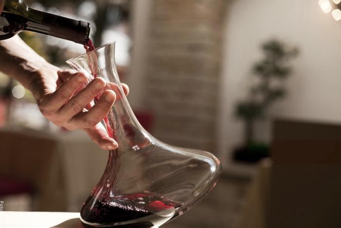 Foto de un hombre sirviendo vino en una jarra