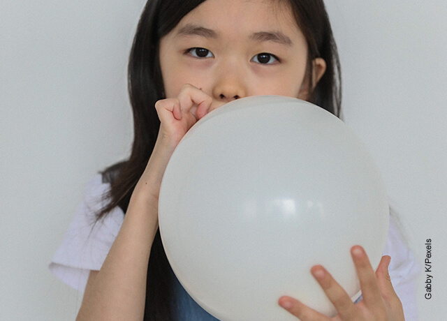 Foto de una niña inflando una bomba que ilustra cómo hacer un arco de globos
