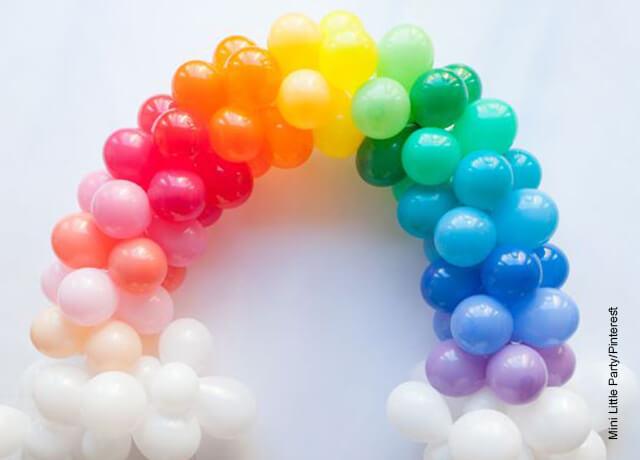 Foto de un arco de globos de muchos colores pegado en una pared