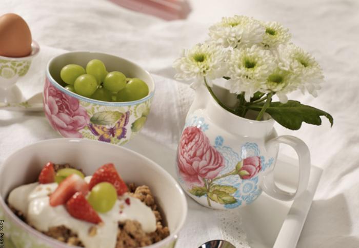 Foto de una taza con flores en una bandeja y frutas