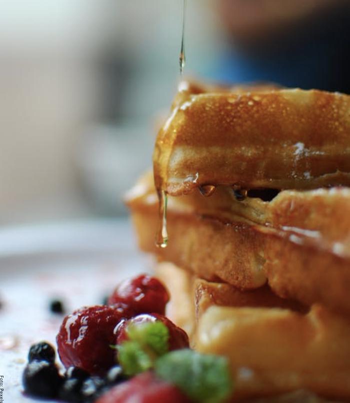 Foto de unos pancakes con miel y frutas