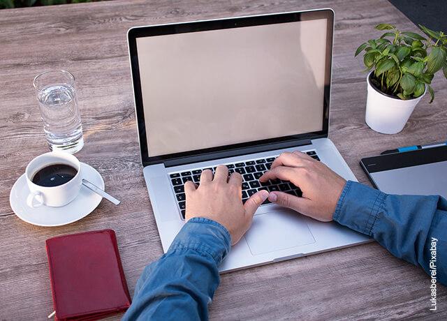 Foto de un hombre escribiendo en su ordenador portátil