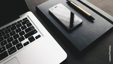 Foto de una computador y un celular sobre un escritorio