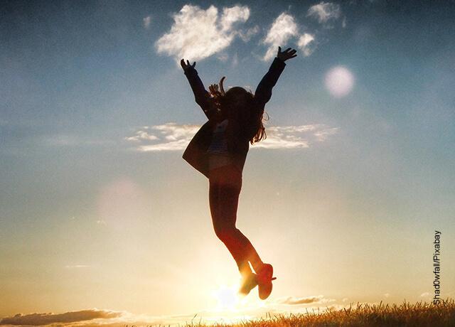 Foto de una mujer saltando en una pradera que muestra cómo hacer un objetivo